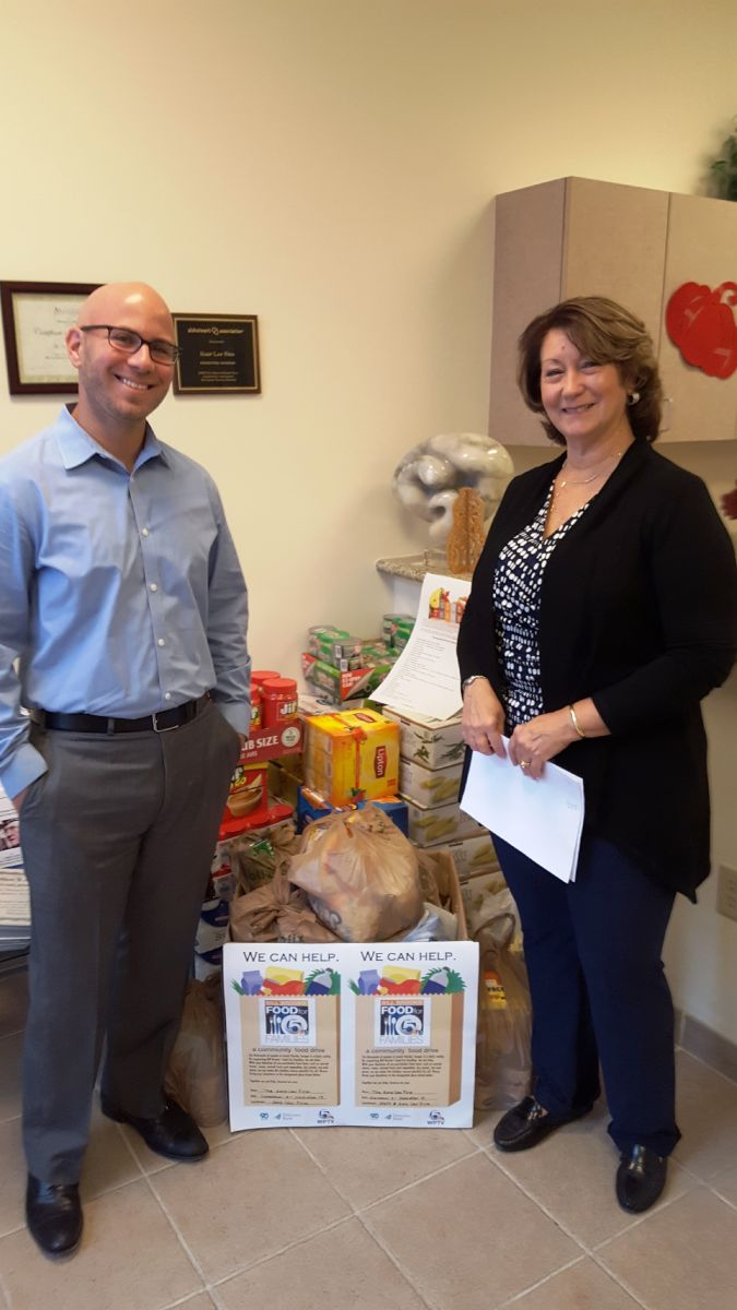 Attorney Jonathan Karp and Paralegal Janet Suarez with the 452 pounds of food our firm contributed to the community food drive