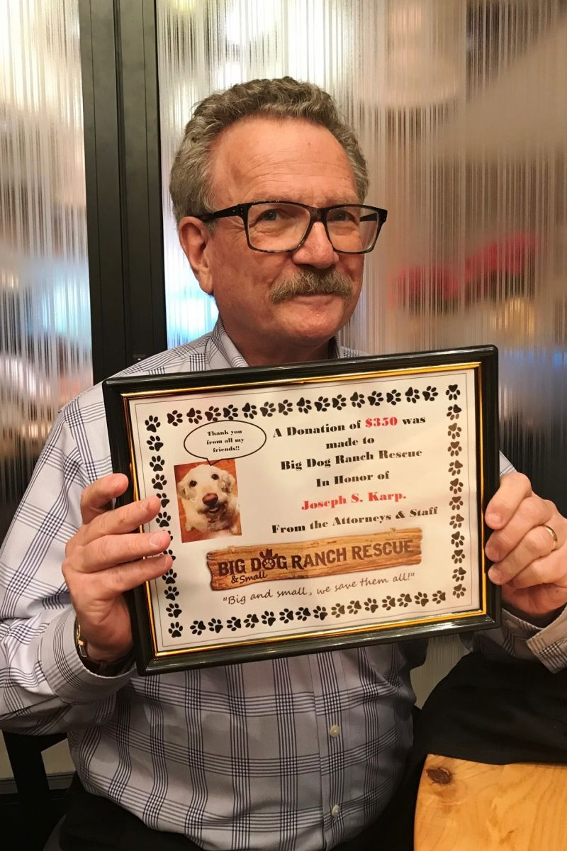 Joseph Karp shows off his holiday present from attorneys and staff: a donation in his honor to Big Dog Ranch Rescue